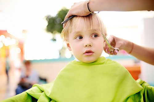 Preschooler boy getting haircut. Children hairdresser with professional tools - comb and scissors. Cutting hair for kids.